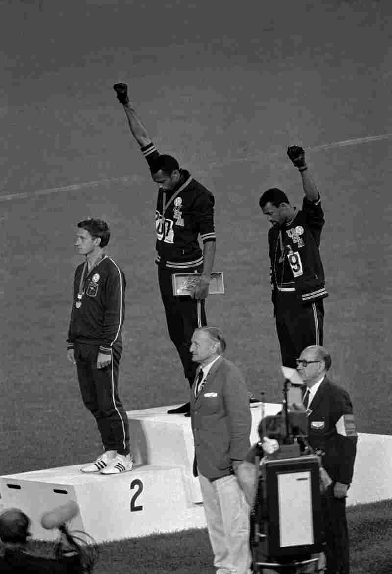"Athletes Tommie Smith (top center) and John Carlos (top right) extend their fists during the playing of ""The Star-Spangled Banner"" after Smith received the gold and Carlos the bronze for the 200-meter run at the 1968 Summer Olympic Games in Mexico City."