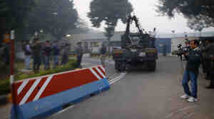 Indian workers in New Delhi remove a barricade Tuesday that had been erected outside the main entrance of the U.S Embassy as a safety measure.