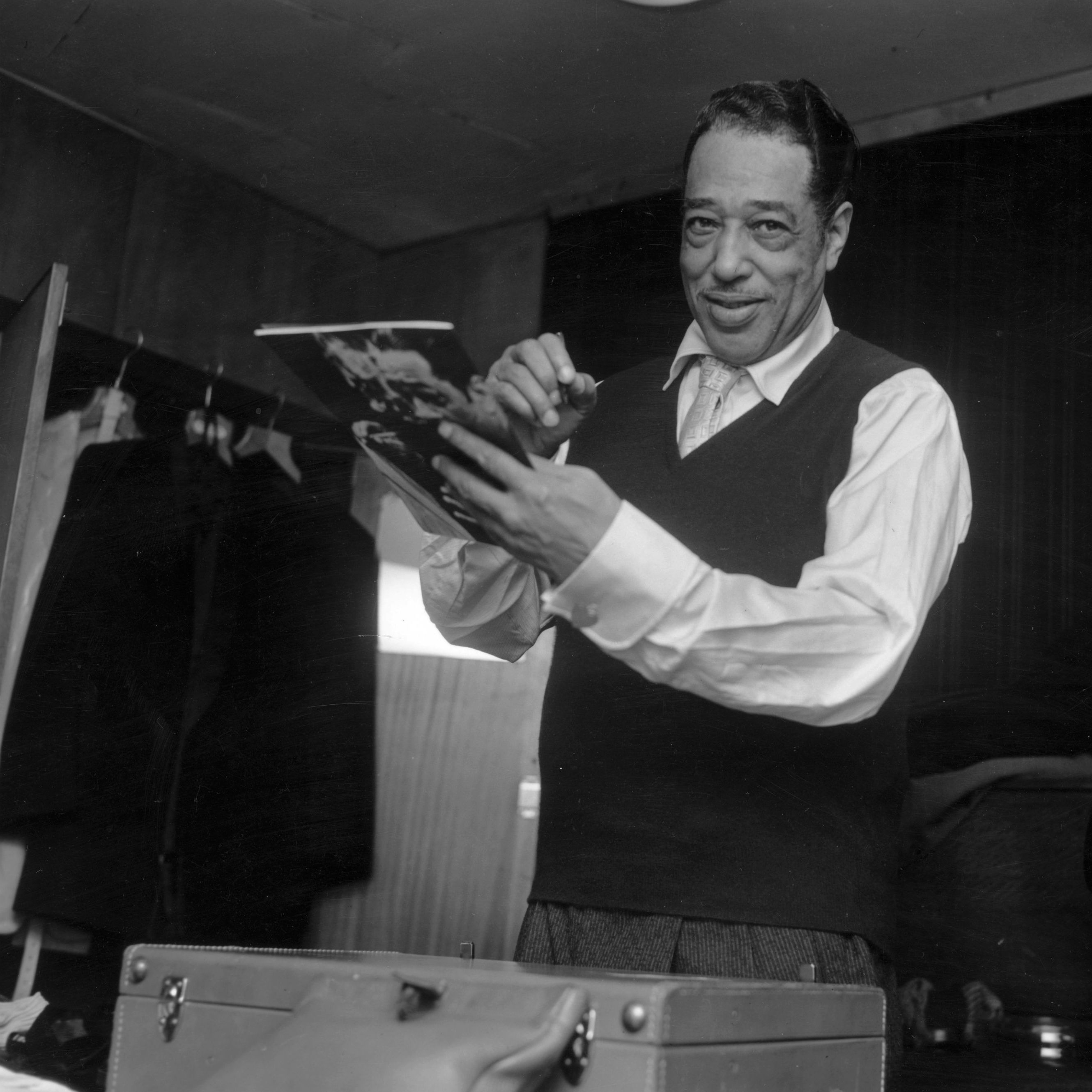Duke Ellington signs his biography in London in 1958, with Billy Strayhorn in the background. Ellington and Strayhorn collaborated to create 1960's The Nutcracker Suite.