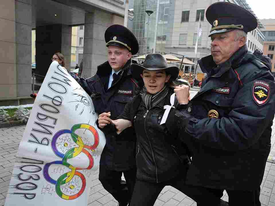 """Sept. 25: Police detain a gay rights activist in Moscow. The poster, adorned with Olympic rings, reads """"Homophobia is the shame of Russia!"""""""