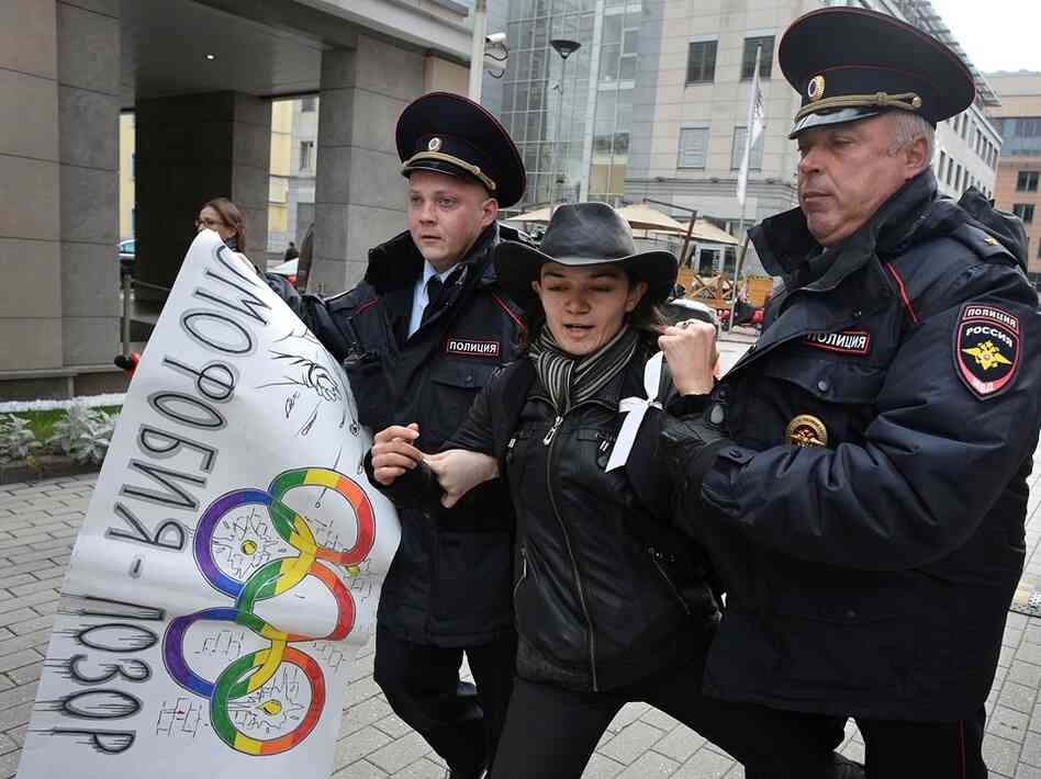 "Sept. 25: Police detain a gay rights activist in Moscow. The poster, adorned with Olympic rings, reads ""Homophobia is the shame of Russia!"""