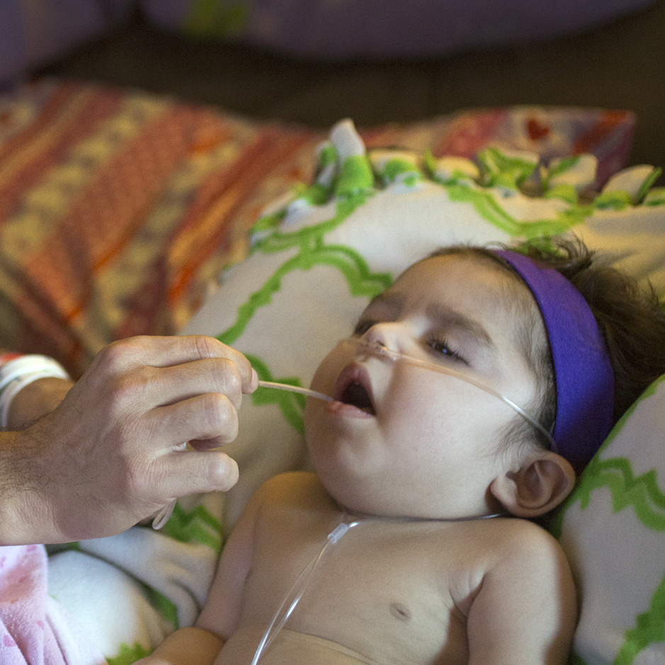 Anthony Shaffer uses a suction device to clear the mouth of Jaylah Donaire-Bechtel, in Harrisburg, Pa. Jaylah has Krabbe disease and can't swallow or speak.