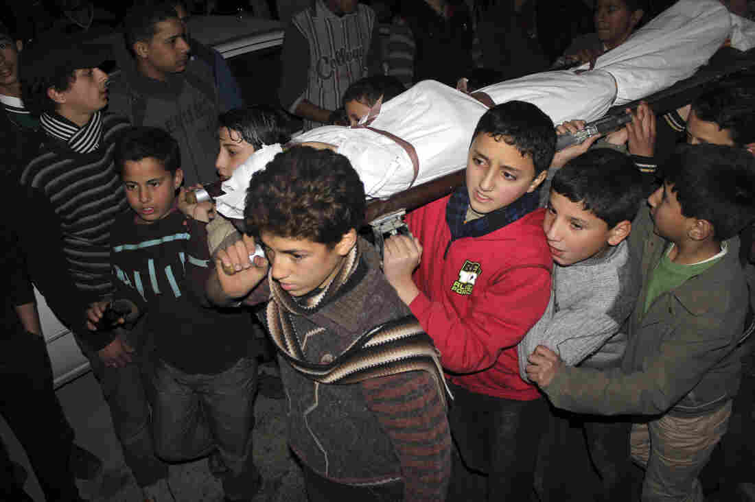 Children carry the body of a friend who was killed by shelling during heavy fighting between the Free Syrian Army and the forces of Syrian President Bashar Assad in Damascus earlier this year.