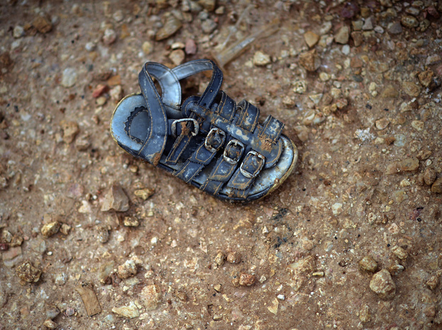 A child's shoe is left in the mud in the Zaatari refugee camp in Jordan. Even for the survivors, childhood vanishes.