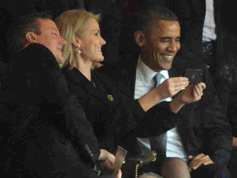 "President Obama and British Prime Minister David Cameron pose for a ""selfie"" with Danish Prime Minister Helle Thorning Schmidt during the memorial service for Nelson Mandela."