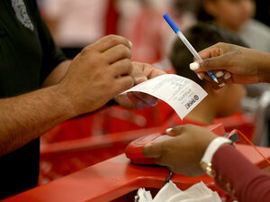 A customer prepares to sign a credit card slip Thursday at a Target store in Miami. The giant retailer says 40 million payment cards nationwide may have been compromised by data theft.