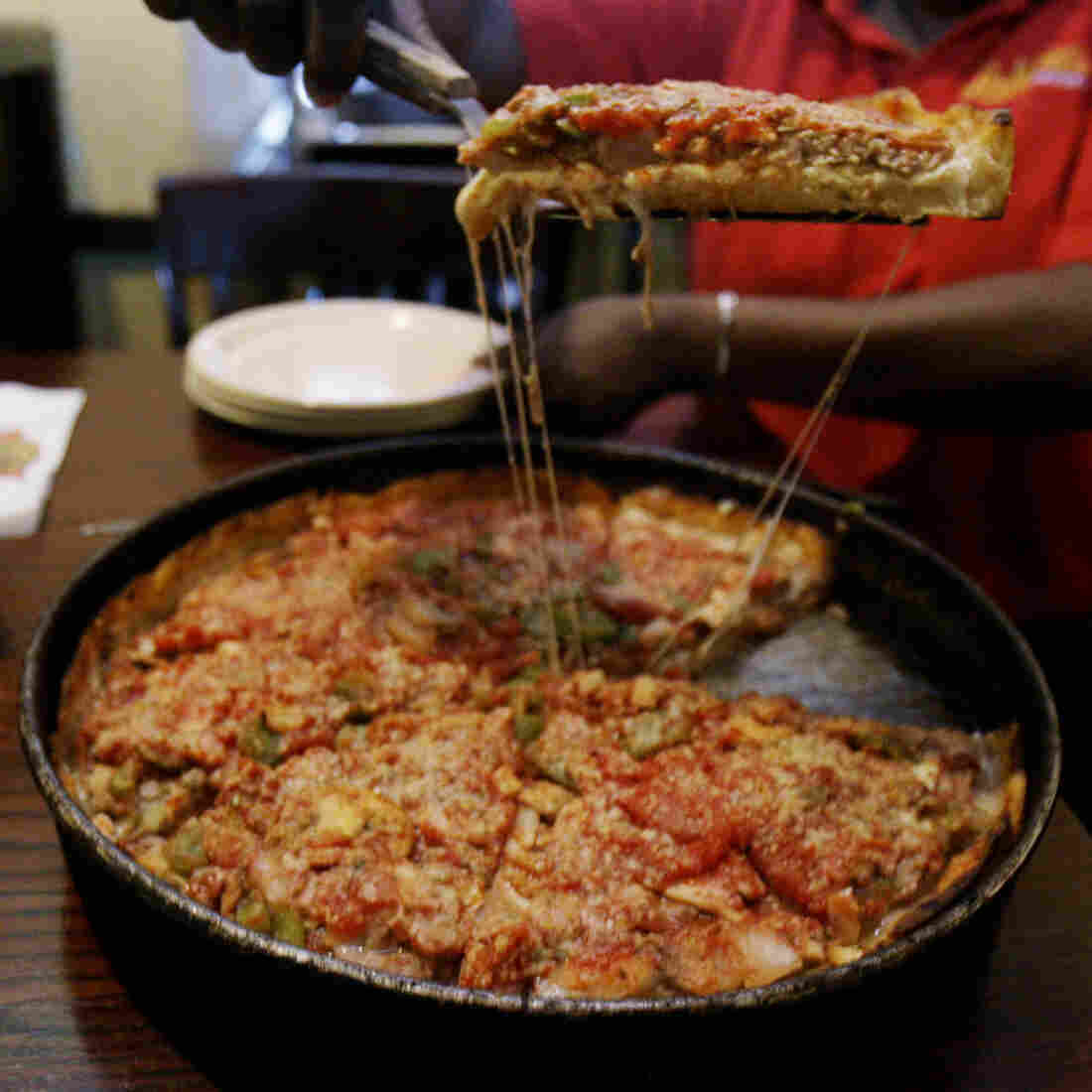 A server dishes up a slice of deep-dish pizza at Lou Malnati's Pizzeria in Chicago. The 1-1/2-inch thick legendary pie, loaded with sausage, mushrooms, pepperoni and onions, was invented in Chicago.