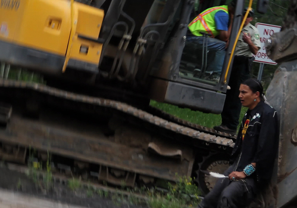 Navajo activist Klee Benally chains himself to an excavator on the San Francisco Peaks, which he and 13 tribes consider sacred.