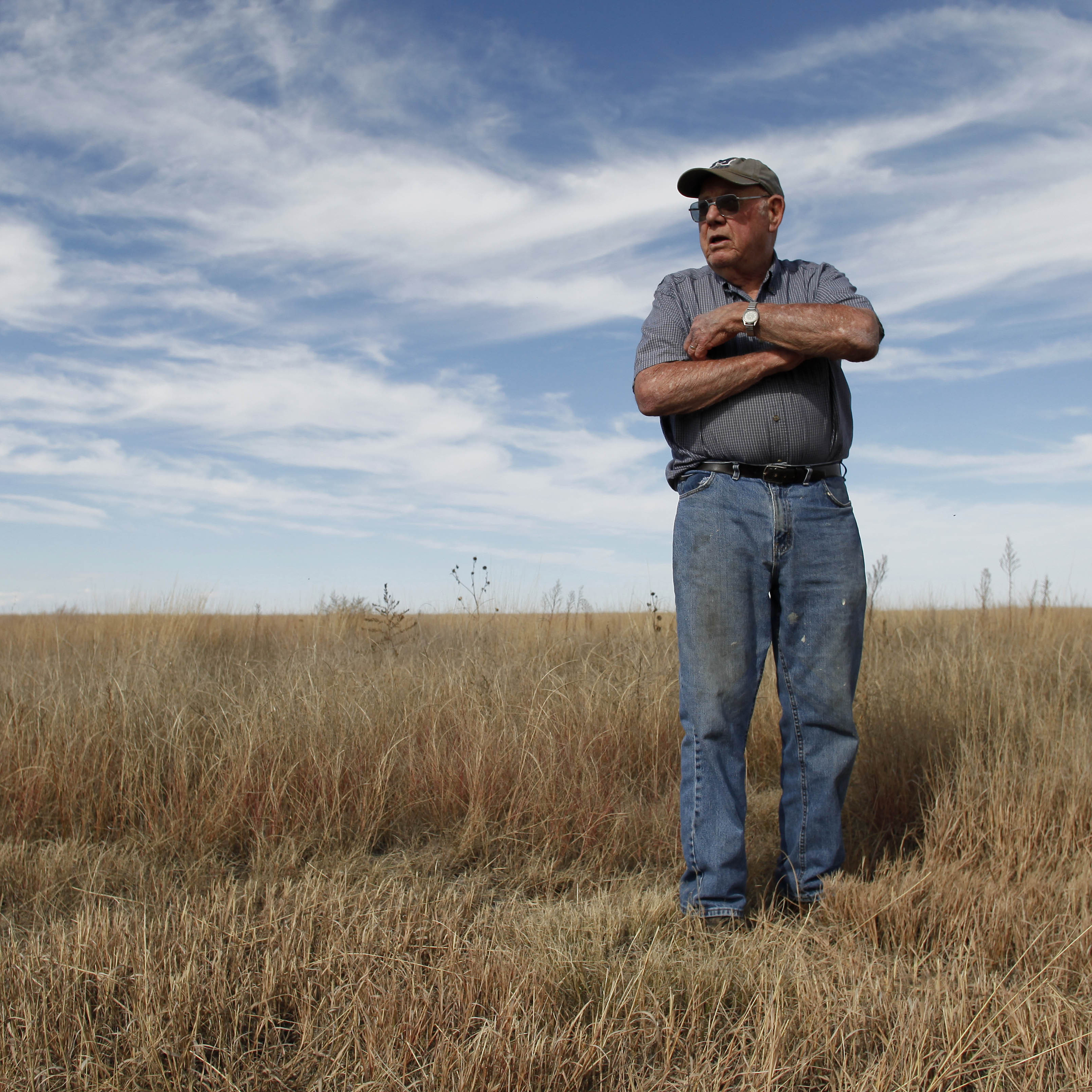 Retired farmer Joe Govert stands on a parcel of family's land near Tribune, Kan., which the government had paid him to keep covered with native grasses.
