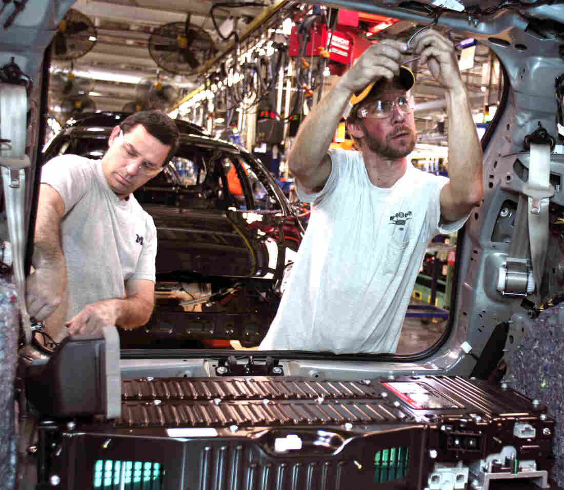 At a Ford plant in Michigan, workers load a battery into a Ford C-MAX plug-in hybrid vehicle. The economy picked up speed in the third quarter. Economists caution, though, that it may slow in coming quarters.