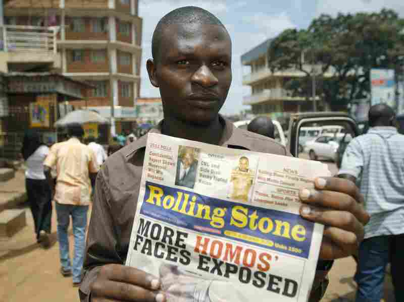 Giles Muhame, managing editor of the Ugandan publication Rolling Stone, holds up a November 2010 issue of the newspaper in Kampala, after it published the names and photos of 14 men it identified as gay.