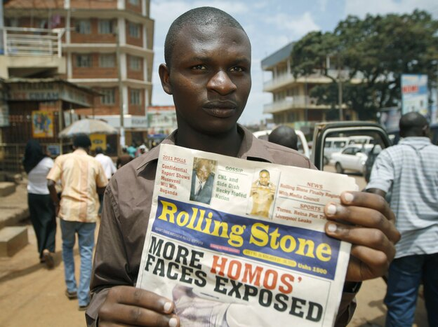 Giles Muhame, managing editor of the Ugandan publication <em>Rolling Stone</em>, holds up a November 2010 issue of the newspaper in Kampala, after it published the names and photos of 14 men it identified as gay.