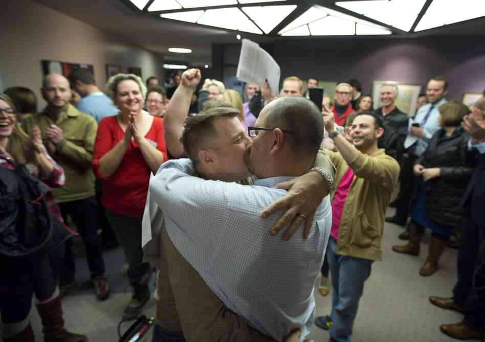Chris Serrano, left, and Clifton Webb kiss after being married, as people wait in line to get licenses outside of the marriage division of the Salt Lake County Clerk's Office in Salt Lake