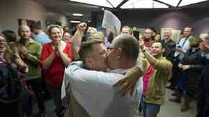 Chris Serrano, left, and Clifton Webb kiss after being married, as people wait in line to get licenses outside of the marriage division of the Salt Lake County Clerk's Office in Salt Lake City on Friday.
