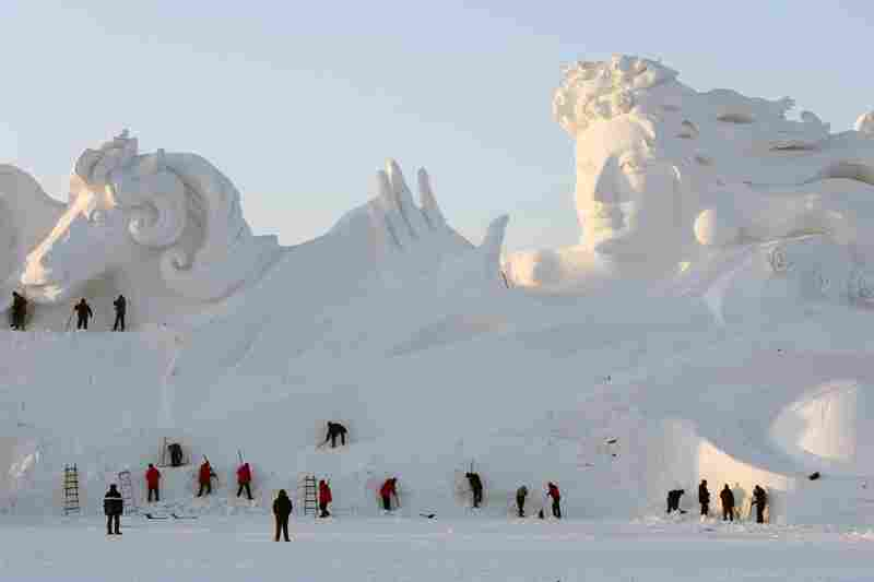 Workers carve a 117-meter-long and 26-meter-high large snow sculpture for the 26th China Harbin International Snow Sculpture Art Expo in Harbin.