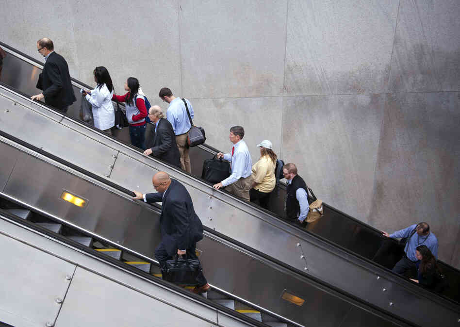 People exit a Metro subway station, by escalator, along Pennsylvania Ave., NW, in Washington.