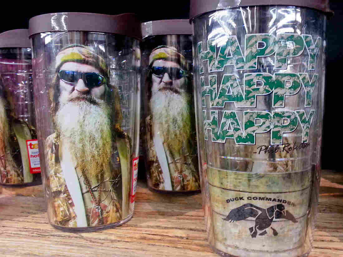 Duck Dynasty plastic drinking glasses with Phil Robertson's image are among the merchandise on sale at the Duck Commander store in West Monroe, La., and at other businesses around the nation.