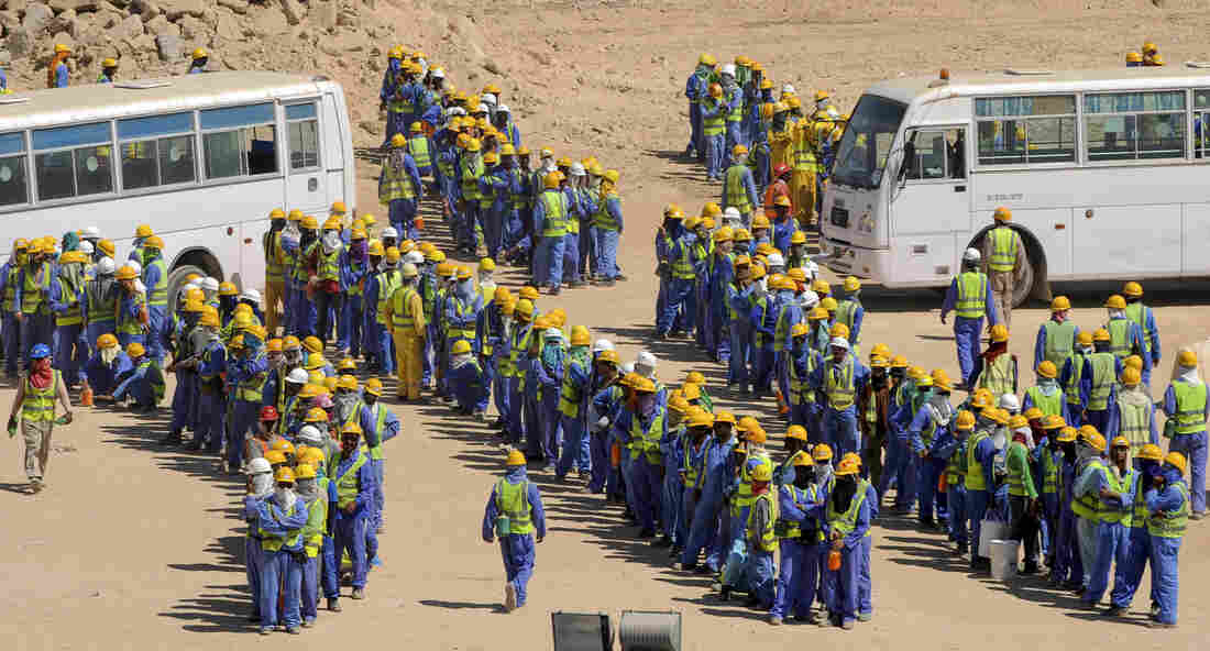 Foreign construction workers line up for the bus back to their housing camp in Doha, Qatar, on Nov. 19. Amnesty International says workers often face problems with the nonpayment of wages, harsh and dangerous working conditions, and poor housing.