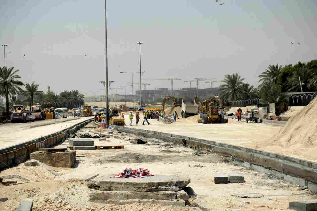 Foreign laborers work on a new road in Doha, Qatar, on Oct. 4. Recent reports have said that construction workers in Qatar have been subject to abuse and harsh working conditions.