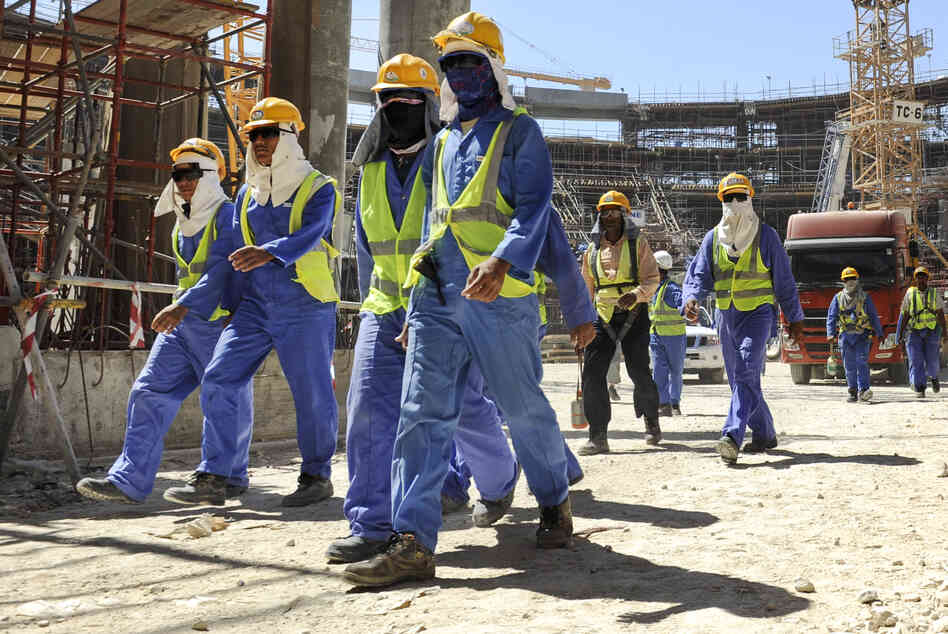 Foreign construction workers leave a work site in Qatar's capital Doha on Nov. 19. Soccer's ruling body, FIFA, says it will put pressure on Qatar, the host of the 2022 World Cup, over the conditions of migrant workers in the construction sector.