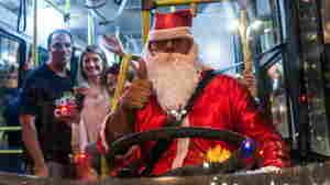 A driver disguised as Santa Claus drives a public bus at Paulista Avenue in Sao Paulo, Brazil.