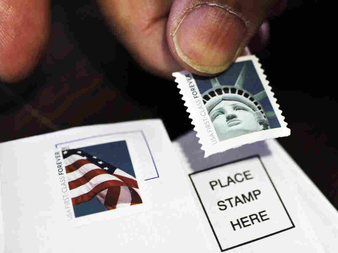A customer places first-class stamps on envelopes at a U.S. Post Office in San Jose, Calif. It'll cost another 3 cents to send a first-class letter starting on Jan. 26.