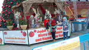 A Palestinian family poses for pictures by the creche in Bethlehem's Manger Square.