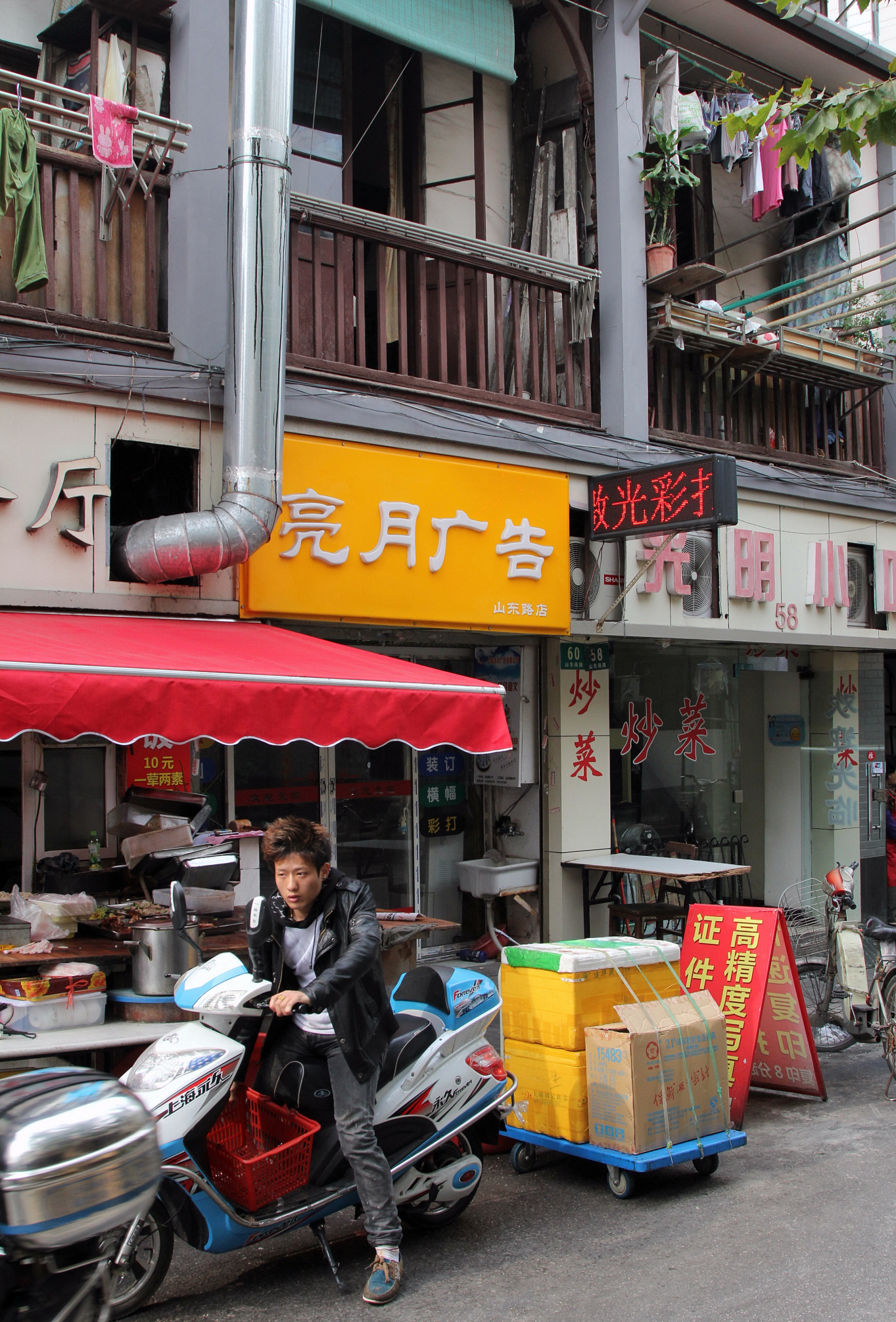 Qiu grew up in the house above the yellow sign here in the heart of Shanghai.