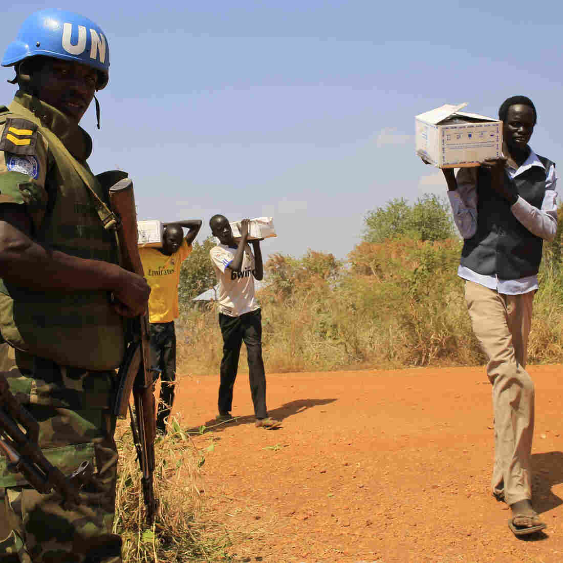 Troops sent to South Sudan by the U.N. watch as men walk to a camp for refugees near Juba, the nation's capital.