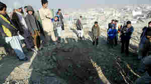 Afghans stand near a crater from an attack reportedly targeting the U.S. Embassy in Kabul on Wednesday.
