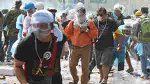 Anti-government protesters flee from tear gas sprayed by police in Bangkok on Thursday.