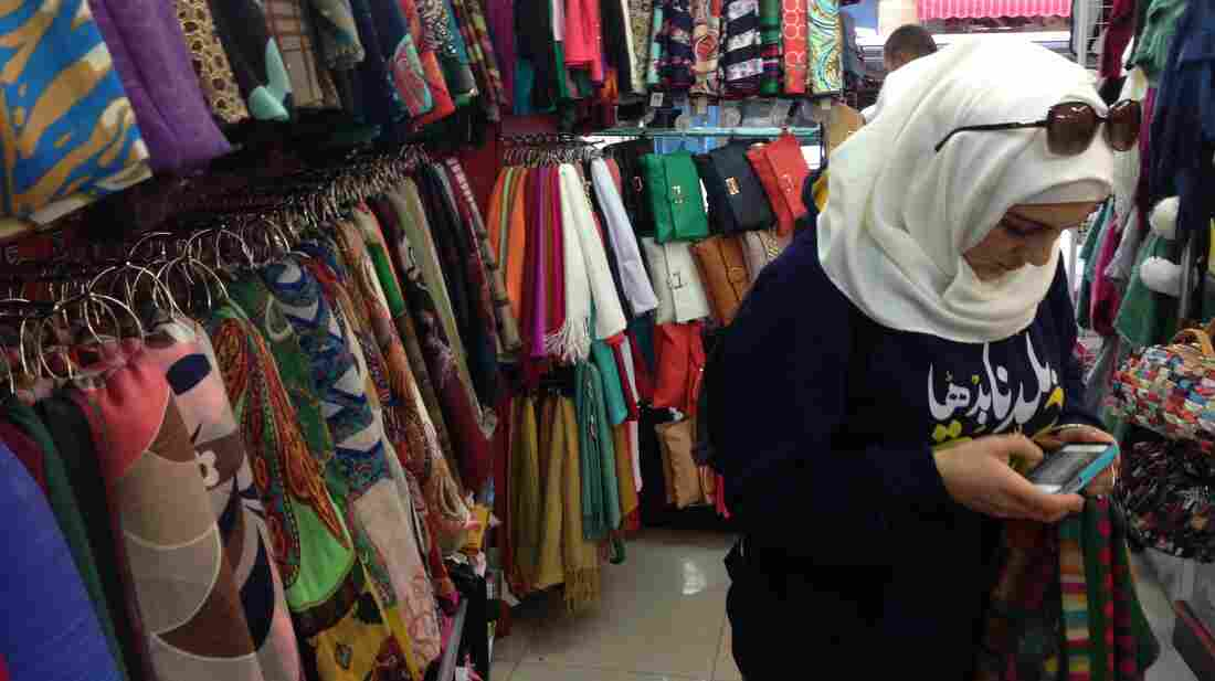 Palestinian Aya Sharaf texts a friend about a perfect $20 headscarf for sale just off the storied Saleh-ad Din Street in East Jerusalem. Sharaf loves new headscarves and buys them all the time.