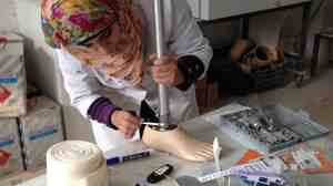 A staff member at the clinic in southern Turkey works on a prosthetic leg that will be given to a victim of Syria's civil war.