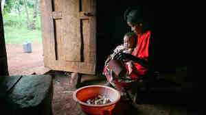 Almaz Acha sits with her baby Alentse at her home in the rural community of Sadoye, in southern Ethiopia. Families in rural communities, like this on