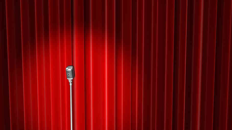 An old style microphone on stage in front of red velvet curtains.