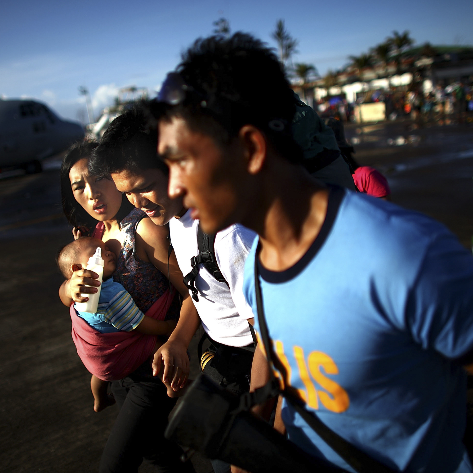 A Filipino family runs across the tarmac of the airport in the devastated city of Tacloban while trying to make it on to a emergency evacuation flight on Nov. 15.