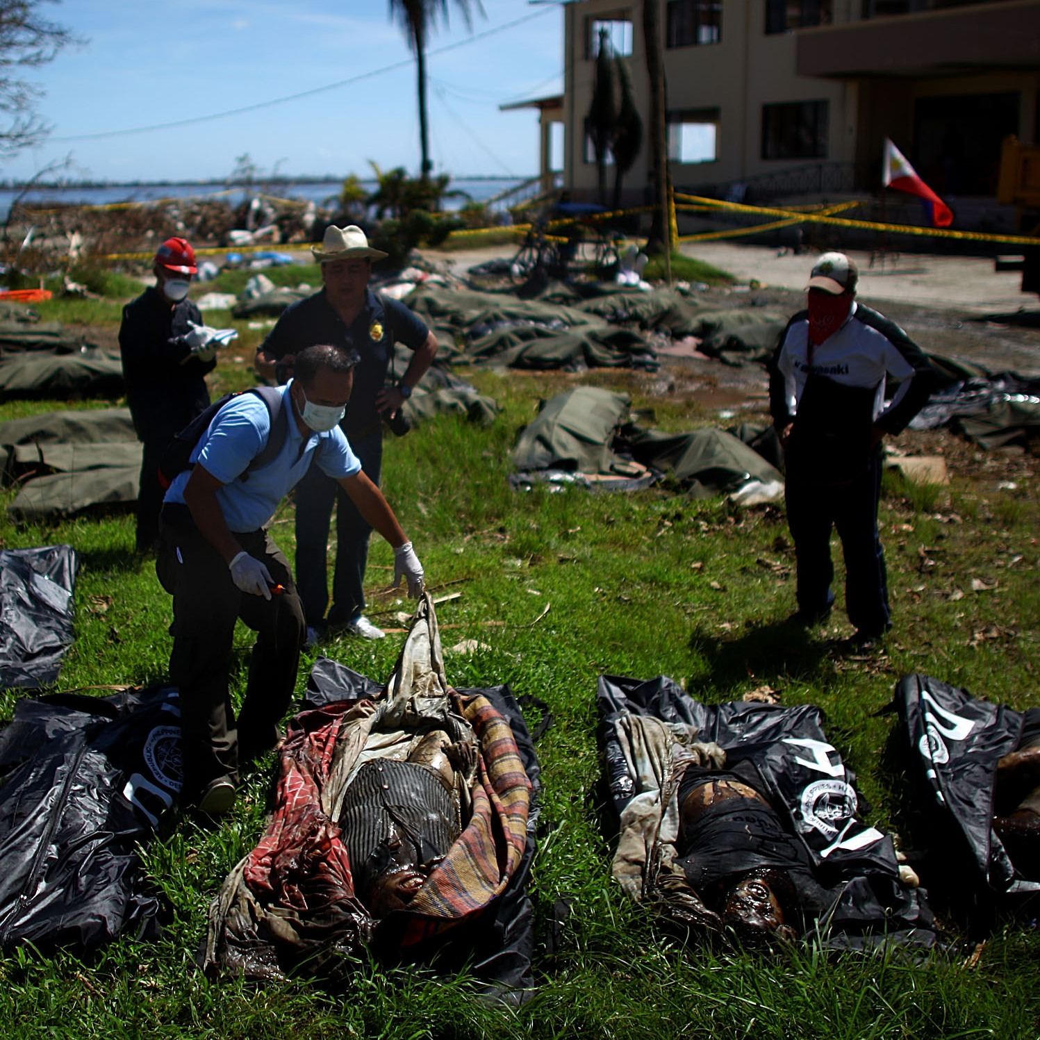 Filipino coroners examine the rotting remains of bodies left at a makeshift morgue outside Tacloban's City Hall.