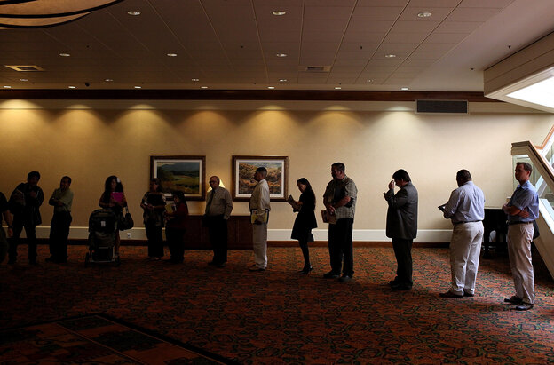Job seekers read pamphlets as they wait in line to enter a job fair in San Jose, Calif.