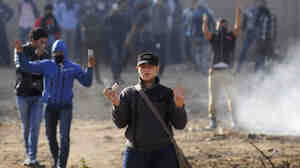 Supporters of the Muslim Brotherhood at Al-Azhar university make the four-finger Rabaa gesture as they hold tear gas canisters during clashes with riot police and residents of the area at the university's campus in Cairo on Saturday.