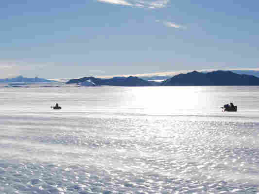 Members of the Antarctic Search for Meteorites team drive their snowmobiles across an expanse of blue ice, hoping to spot meteorites that fell to Earth long ago.