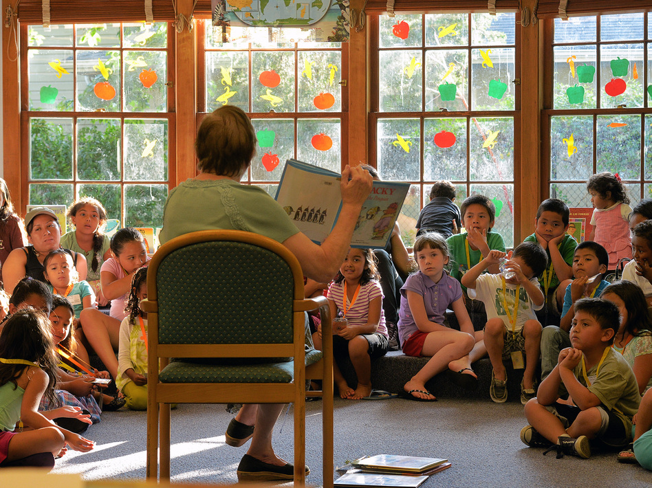 In Virginia this summer, Arlington Public Schools transported students in poor neighborhoods to community libraries for group readings. Studies say children from low-income families may hear roughly 30 million fewer words by age 3 than their more affluent peers. (Bill O'Leary/The Washington Post/Getty Images)