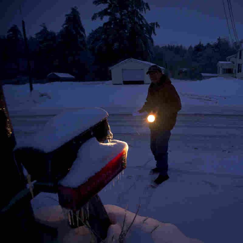 Maine resident Jim Ridley uses a flashlight to get his mail Thursday. Thousands may be without power well into next week if snow and ice hit the state Sunday night.