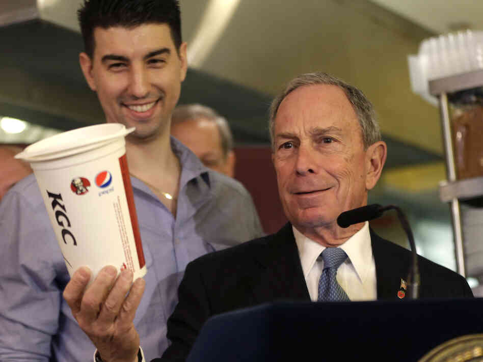 New York City Mayor Michael Bloomberg holds a 64-ounce cup, as Lucky's Cafe owner Greg Anagnostopoulos stands behind him during a news conference at the cafe in New York.