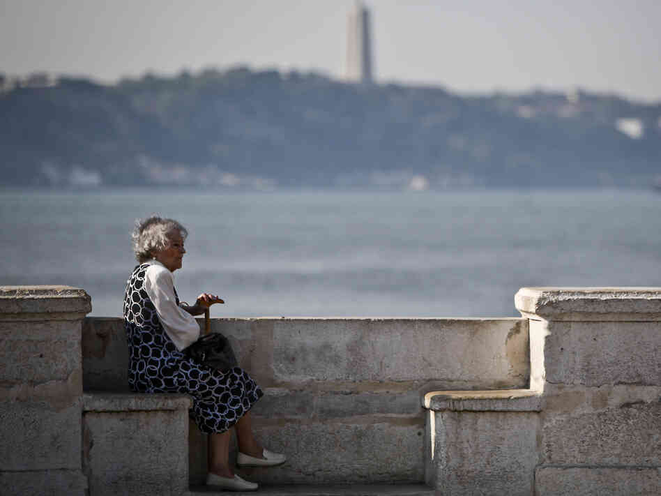 An elderly woman sits near the Tejo River in Lisbon on Oct. 17, 2011. Portugal's population is aging rapidly, due to a drop in births coupled with growth in emigration.