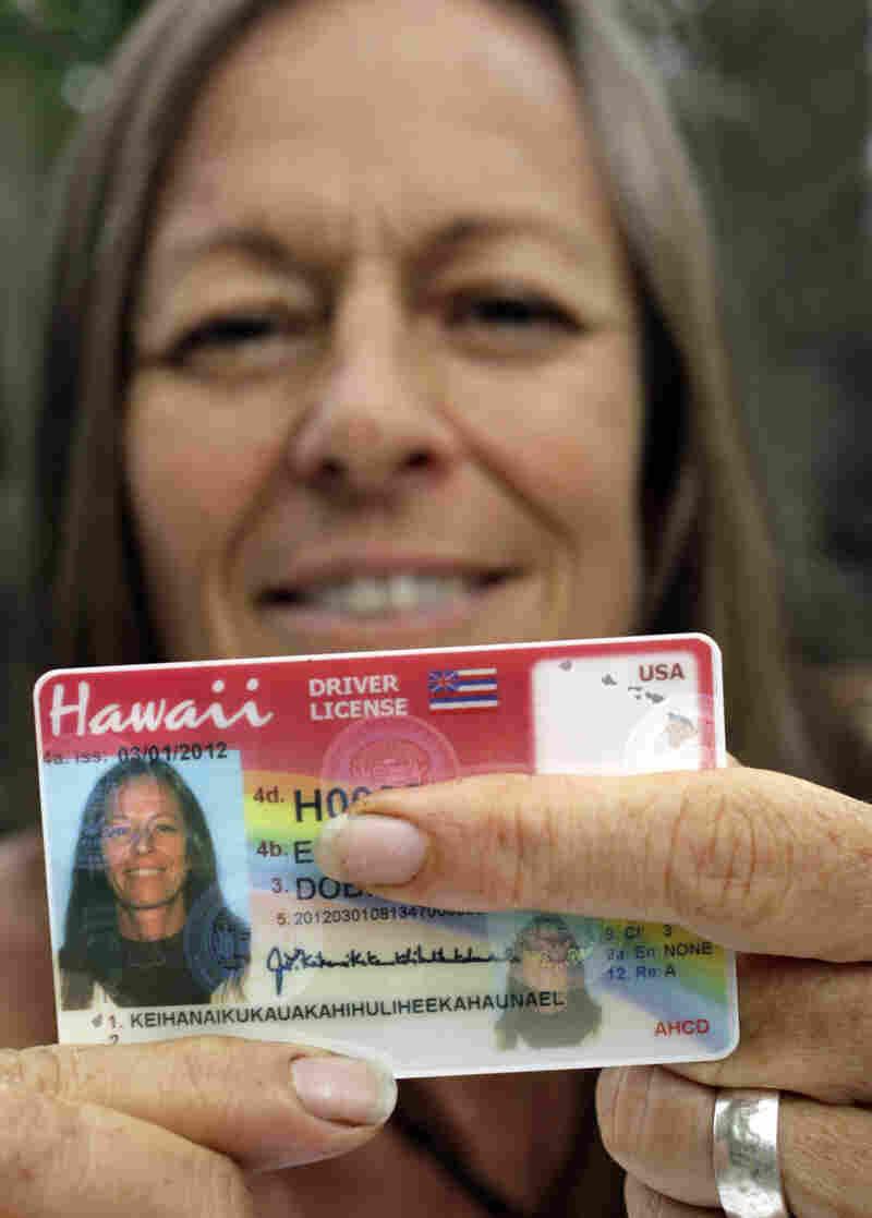Janice Keihanaikukauakahihulihe'ekahaunaele holds her old Hawaii drivers license that lacked the space for her full name.