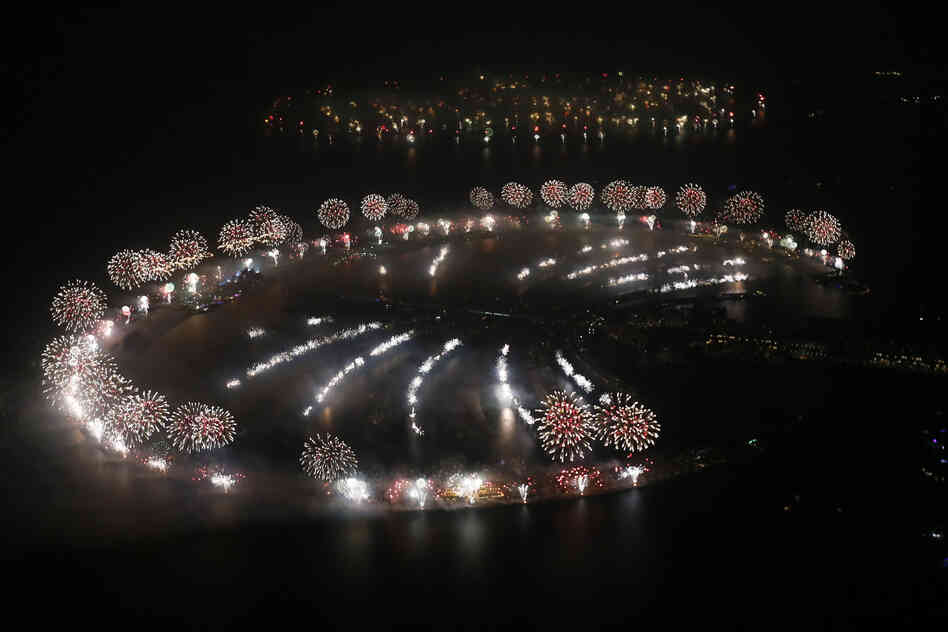 Fireworks explode over Palm Jumeirah in Dubai to celebrate the new year in a dazzling bid for a new world record. The glittering firework