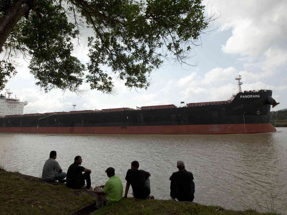 Men sit by the side of the Panama Canal as a ship sails past in Gamboa near Panama City, last month. The expansion project is aimed at accom