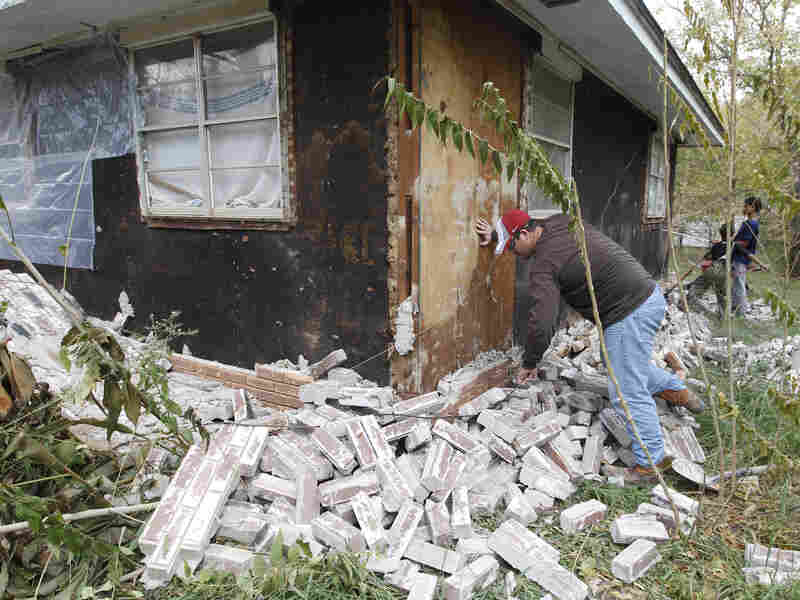 Chad Devereaux cleans up bricks that fell from his in-laws' home in Sparks, Okla., in November 2011, after two earthquakes hit the area in less than 24 hours.