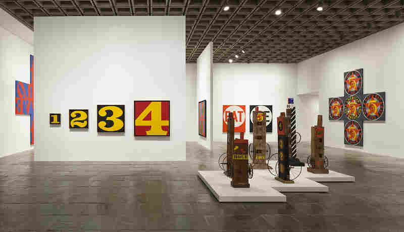 "The Whitney describes its retrospective as revealing ""an artist whose work, far from being unabashedly optimistic and affirmative, addresses the most fundamental issues facing humanity — love, death, sin and forgiveness."" [Left to right: Exploding Numbers (1964-66); Hole (1960); Five (1984).]"