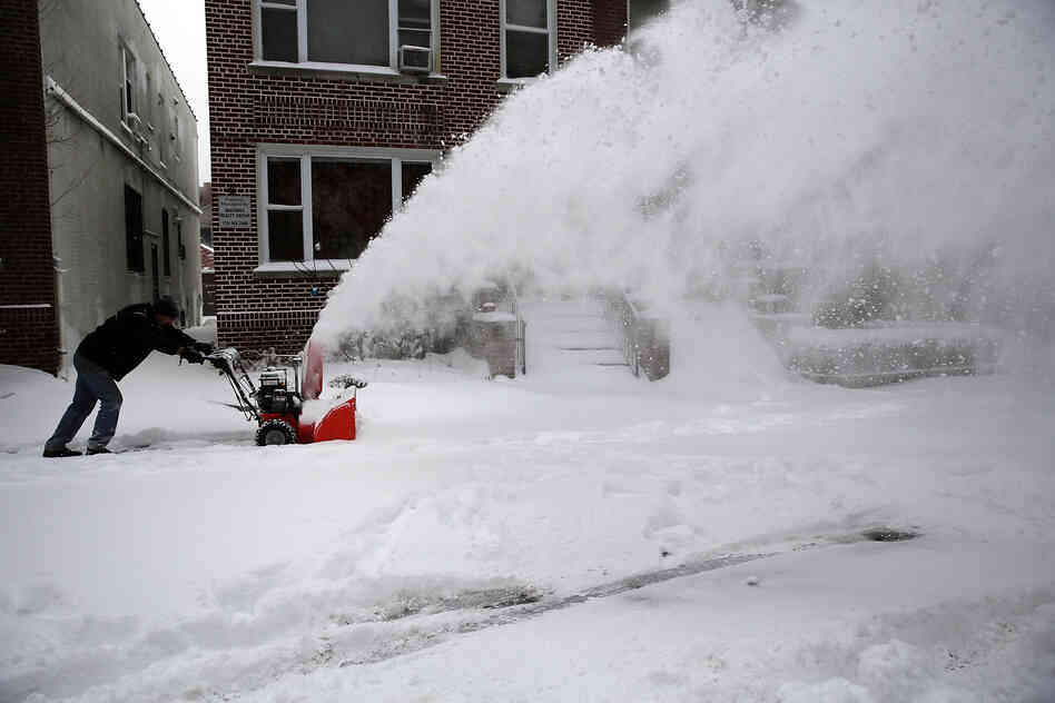 A man clears snow from a sidewalk in Brooklyn, N.Y., following a snowstorm that left up to 7 inches of snow Friday.